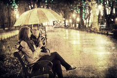 Couple sititng at bench in night lights. Photo in vintage multic Royalty Free Stock Image
