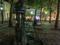 Couple sits on bench in Paris evening at Place Emile Goudeau on Montmartre. A couple sits on a bench on a cobbled square on a Paris summer evening; Place Emile Royalty Free Stock Photo