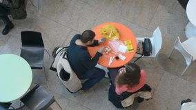 Couple sits at small round tables in Ocean Plaza mall stock video footage