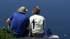 Couple Sitting above Ocean Stock Image