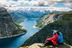 Couple sitting against amazing nature view on the way to Trolltunga. Location: Scandinavian. Mountains, Norway, Stavanger. Artistic picture. Beauty world. The stock photo