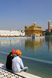 Couple sitting against golden temple Royalty Free Stock Images
