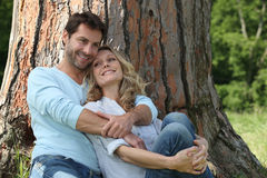 Couple sitting against a tree Royalty Free Stock Photos
