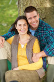 Couple sitting against tree trunk Stock Image