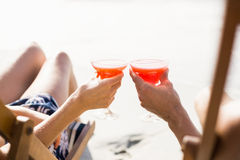 Couple sitting on armchair with cocktail drink. Couple sitting on armchair at beach with cocktail drink Stock Image