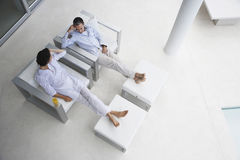 Couple Sitting On Armchairs With Feet On Foot Stools Stock Photo