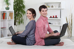 Couple sitting back to back. And working on their laptops Stock Images