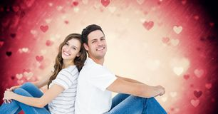 Couple sitting back to back against digitally generated pink background with hearts. Smiling couple sitting back to back against digitally generated pink Stock Images