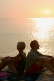 Couple sitting back to back on the beach at sunset. Couple sitting back to back on the beach at sea sunset Royalty Free Stock Images