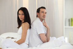 Couple sitting back to back. On the bed Stock Photography