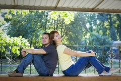 Couple sitting back to back on a bench Stock Images