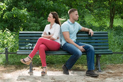 Couple Sitting Back To Back On Bench. Unhappy Couple Sitting Back To Back On Bench In Park Royalty Free Stock Photo