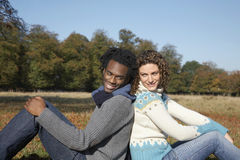 Couple Sitting Back To Back In Field Stock Photography