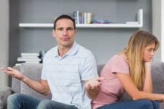 Couple sitting back to back after a fight on the couch with man. Couple sitting back to back after a fight on the couch with men gesturing at camera in sitting Royalty Free Stock Photos