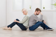 Couple Sitting Back To Back On Floor. Sad Young Couple Sitting Back To Back On Floor At Home Royalty Free Stock Images