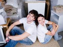Couple sitting back-to-back after moving. Smiling happy young couple sitting back-to-back after moving - high angle Royalty Free Stock Photo