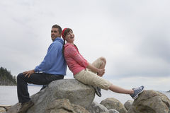 Couple Sitting Back To Back On Rocks Against Ocean. Full length side view of a happy young couple sitting back to back on rocks against ocean Stock Images