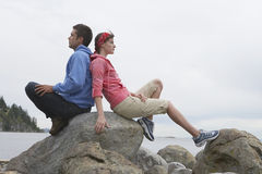 Couple Sitting Back To Back On Rocks Against Ocean. Full length side view of a young couple sitting back to back on rocks against ocean Royalty Free Stock Photos