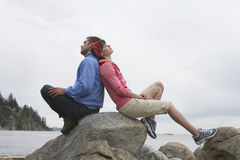 Couple Sitting Back To Back On Rocks Against Ocean. Full length side view of a young couple sitting back to back on rocks against ocean Royalty Free Stock Photo