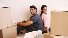 Couple sitting back to back in a room with boxes stock video footage