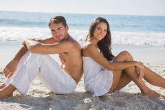 Couple sitting back to back on the sand. At the beach Royalty Free Stock Image