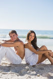 Couple sitting back to back on sand smiling at camera. At the beach Royalty Free Stock Image