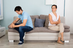Couple Sitting Back To Back On Sofa. Sad Young Couple Sitting Back To Back On Sofa At Home Royalty Free Stock Image