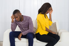 Couple Sitting Back To Back On Sofa. Young Unhappy African Couple Sitting Back To Back On Sofa At Home Stock Photos