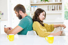 Couple sitting back to back and text messing on mobile phone. At home Royalty Free Stock Image