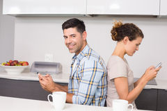 Couple sitting back to back texting with man smiling at camera Stock Photography