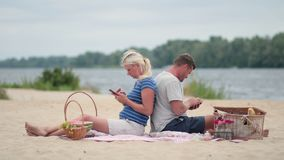 Couple sitting back to back and texting on phone stock video footage
