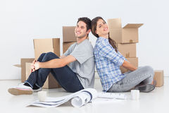 Couple sitting back to back. In their new house Stock Image