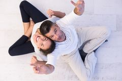 Couple sitting with back to each other on floor. Top view of Cheerful young couple sitting with back to each other on floor Stock Photos