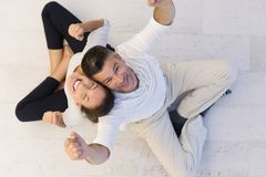 Couple sitting with back to each other on floor. Top view of Cheerful young couple sitting with back to each other on floor Stock Photography