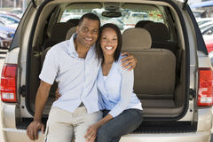 Couple sitting in back of van smiling Stock Photo