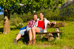 Couple is sitting on a bank with mountain panoram Royalty Free Stock Photos