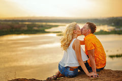 Couple sitting on bank of river at sunset. Kiss. Royalty Free Stock Images