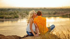Couple sitting on bank of river at sunset. Royalty Free Stock Photo