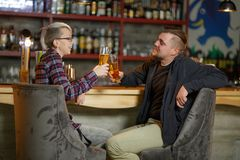 A couple sitting in a bar, chatting and cheers with glasses of beer. Indoors. royalty free stock photos