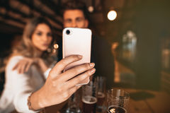 Couple sitting in the bar and taking a selfie Royalty Free Stock Photo