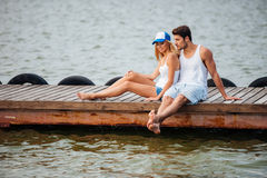 Couple sitting barefoot and talking on pier Stock Photography