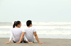 Couple sitting on the beach Stock Images