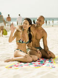 Couple sitting on the beach Stock Image