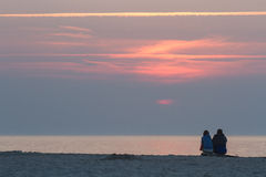 Couple sitting on the beach. Couple admiring the sunset on the beach Royalty Free Stock Image