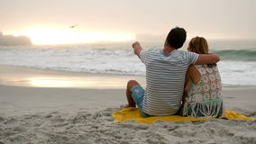 Couple sitting on the beach. Couple sitting on a blanket on the beach stock footage