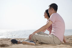 Couple sitting on the beach and looking out at the ocean Royalty Free Stock Photos
