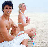 Couple  sitting at the beach practicing yoga Royalty Free Stock Image