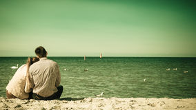 Couple sitting on beach rear view. Loving couple spending leisure time together at beach hugging rear view Royalty Free Stock Photo