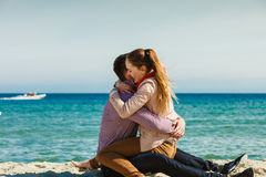 Couple sitting on beach relaxing and hugging Stock Photography