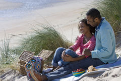 Couple sitting on beach, side view Stock Photography